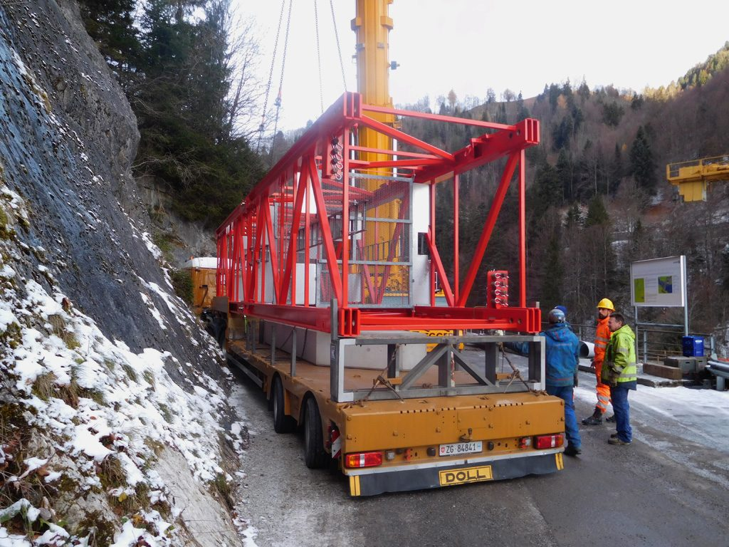 Picture of a truck delivering one of the tower elements on a narrow mountain road